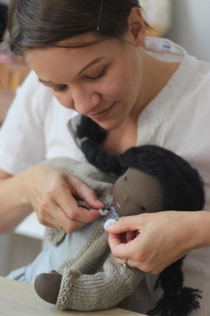 Ich schließe den Knopf an einer Strickjacke von einer Puppe. Resonante Tätigkeiten sind mein liebstes Beispiel für das Gute an der Corona-Krise.
