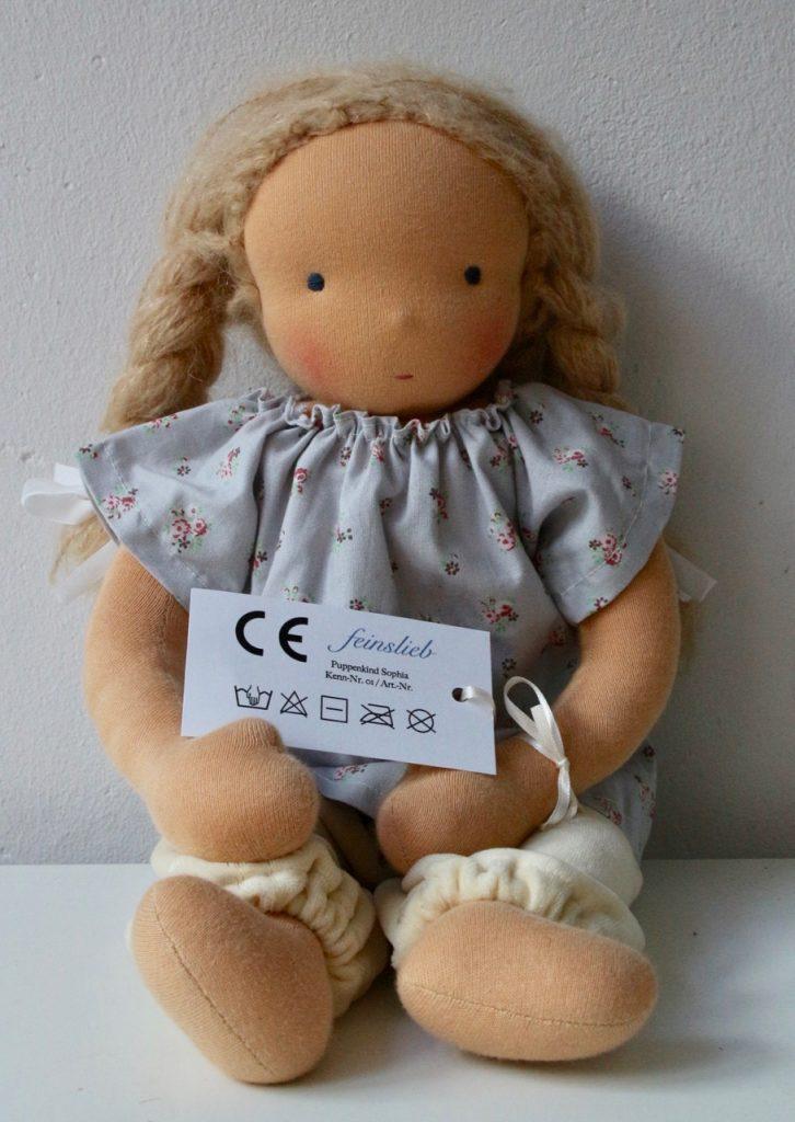 Stoffpuppe / Puppe / Waldorfpuppe mit CE-Etikett. Darauf: Die Textilpflege-Symbole korrekt angeordnet.
