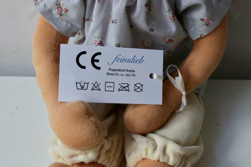 Detail einer Waldorfpuppe / Stoffpuppe / Puppe mit CE-Etikett (Vorderseite). Hier sid die Textilpflege-Symbole richtig dargestellt (Reihenfolge).