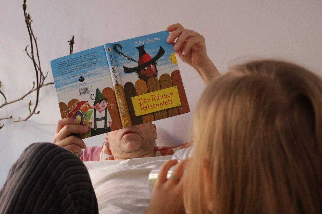 Kind hört bei Räuber Hotzenplotz zu, Vater liest vor.
