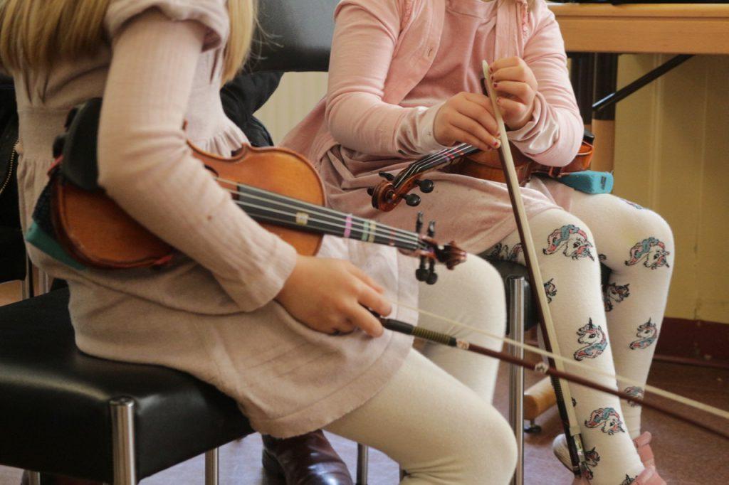 Zwei Kinder mit Geigen (Suzuki-Gruppenunterricht)