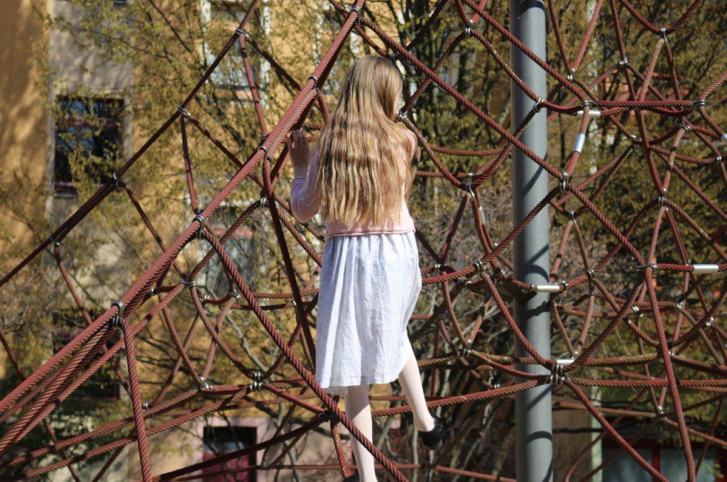 Kind mit Kleid in Kletterspinne, Rückenansicht