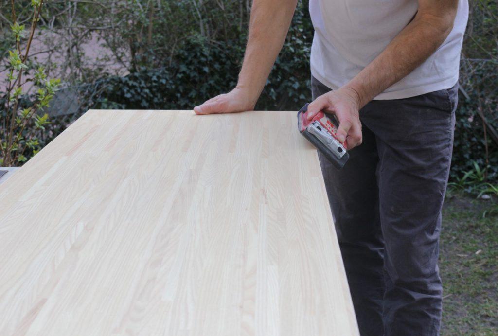 Mann schleift große Holzplatte aus Eichenholz mit Schleifklotz