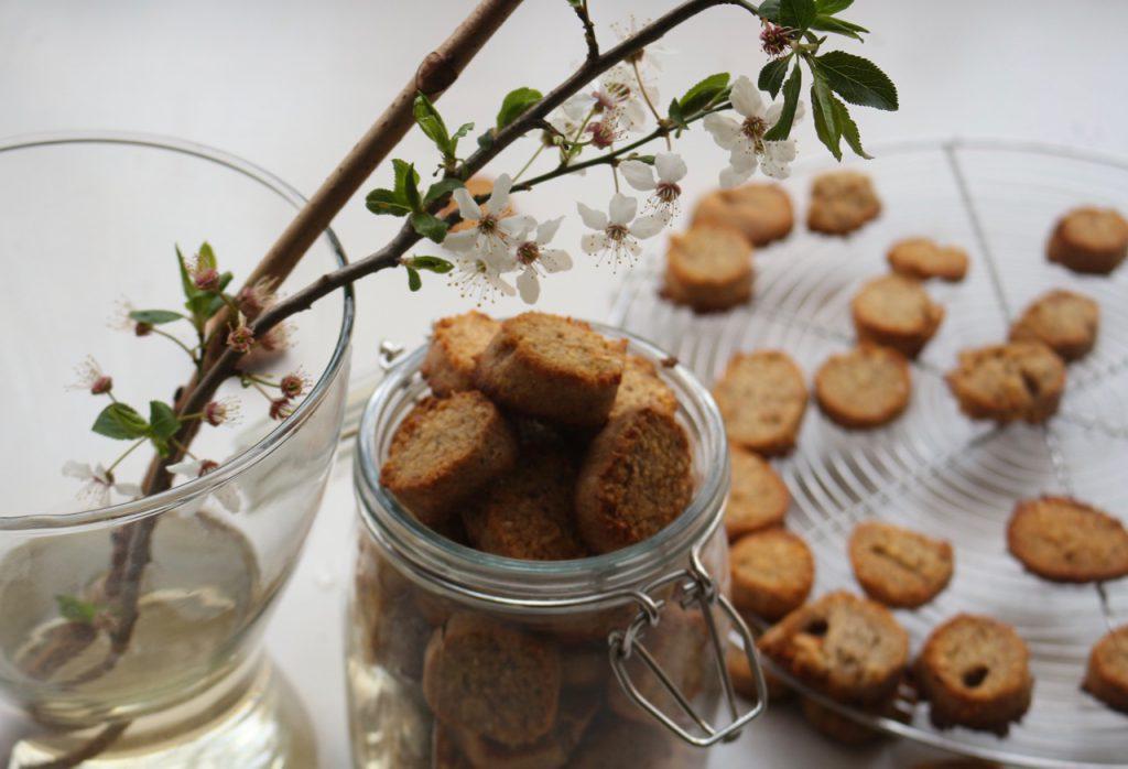 Runde Haselnuss-Kekse in Glas, daneben Vase mit Blütenzweig