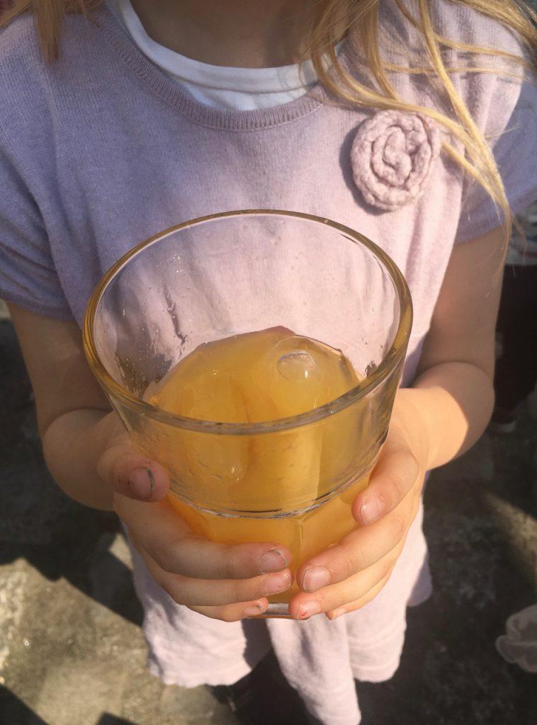Kind mit Orangensaft-Glas