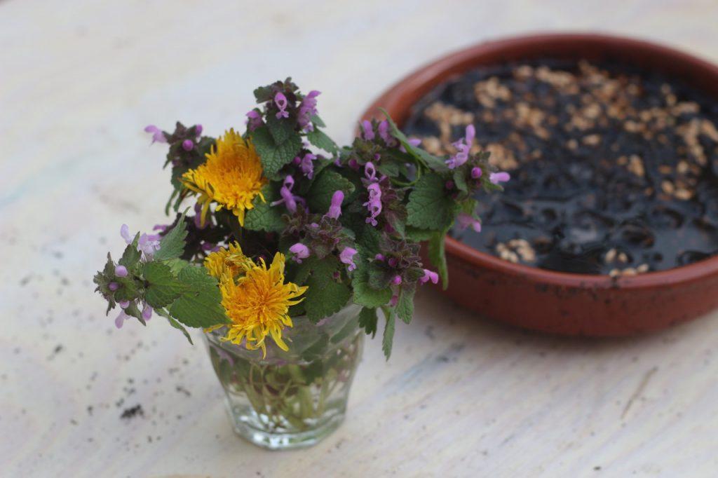 Vorne Blumenstrauß, hinten ausgesätes Ostergras auf Tisch