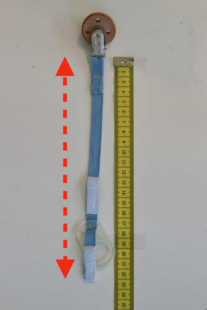 Schnullerketten Länge richtig messen: Schnullerkette (Beispiel) neben Maßband und Pfeil, welche Länge gemessen werden muss.