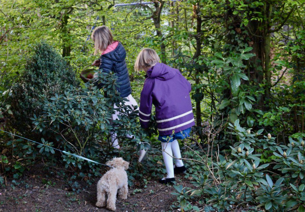 2 Kinder suchen Ostereier, mit Körben in der Hand