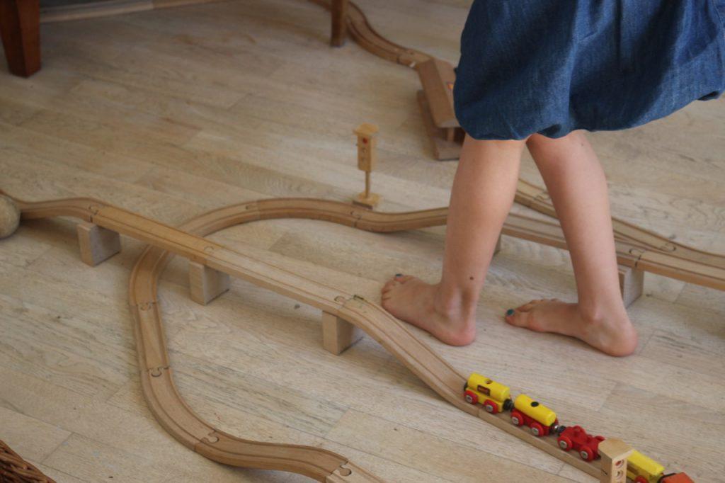Kinderfüße inmitten aufgebauter Brio-Eisenbahn