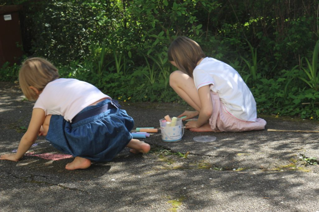 2 Kinder malen mit Sraßenmalkreide vor Grün