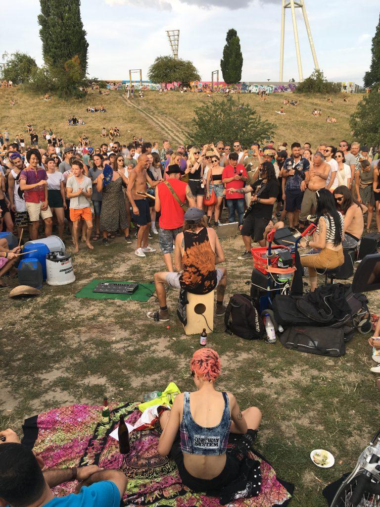 Buntes Menschenvolk tanzt zu alternativen Musikern im Mauerpark