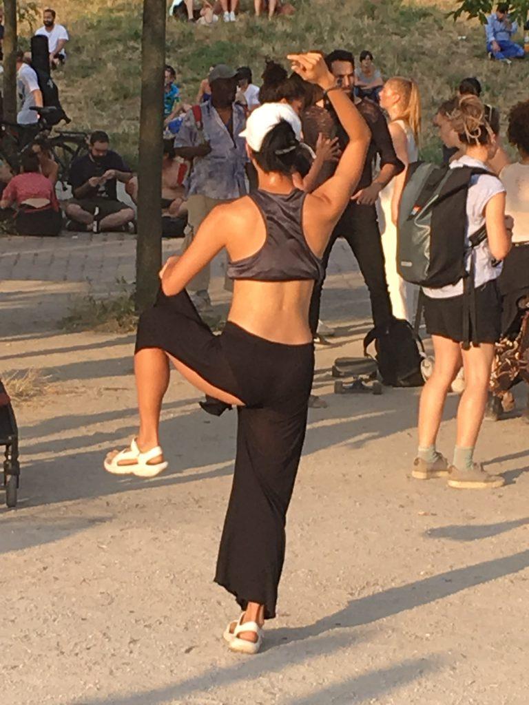 Junge Frau macht Yoga-Übung in schwarzer Hose im Mauerpark Berlin