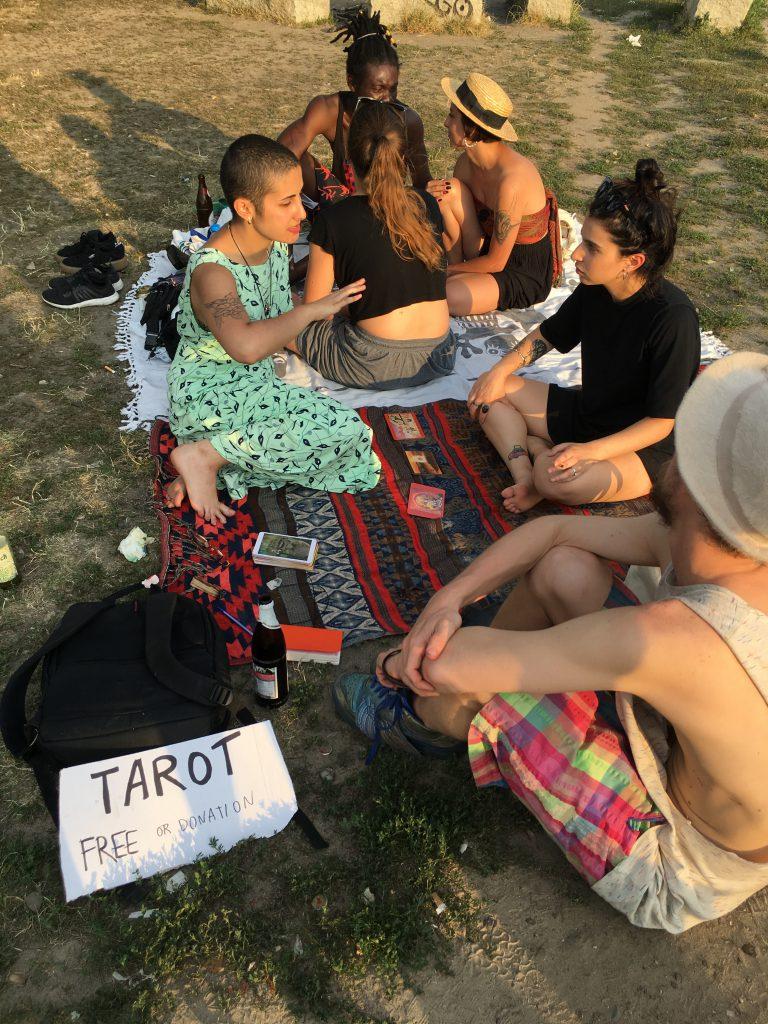 Junge Frau mit Percings und Tattoos legt anderer junger Frau Tarnt-Karten auf dem Grasboden des Mauerparks Berlin