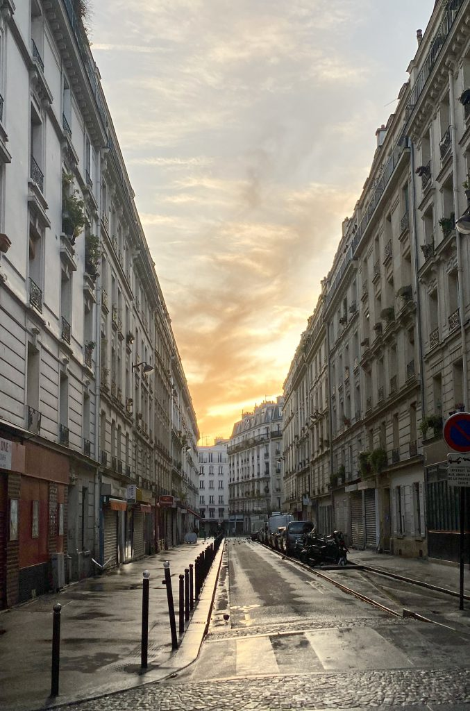 Paris 18. arrondissement: regennasse Straße in Chateau Rouge mit Morgenhimmel