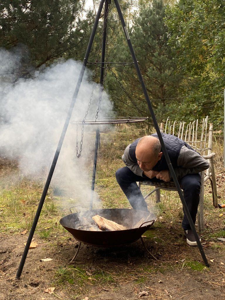 Mann pustet in rauchendes Feuer