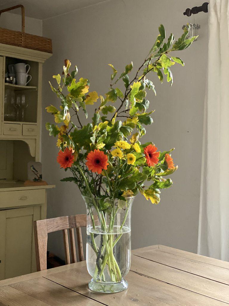 Blumenstrauss mit orangenen und gelben Blüten und gelbem Eichenlaub