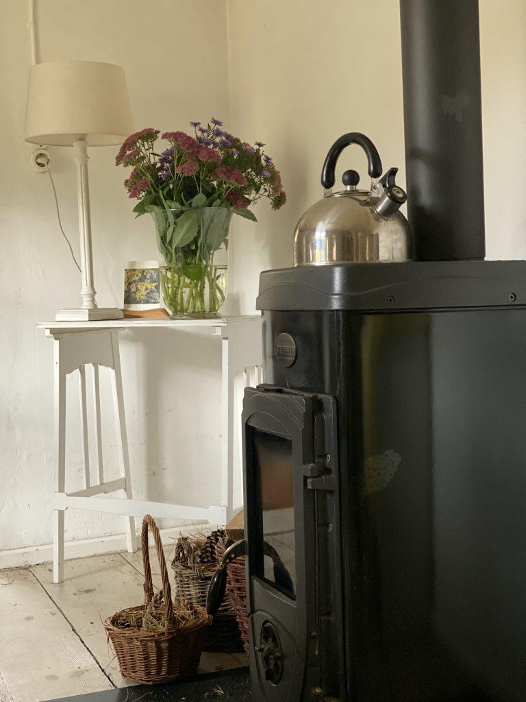 Landhaus-Zimmer mit Ofen und Blumenstrauss