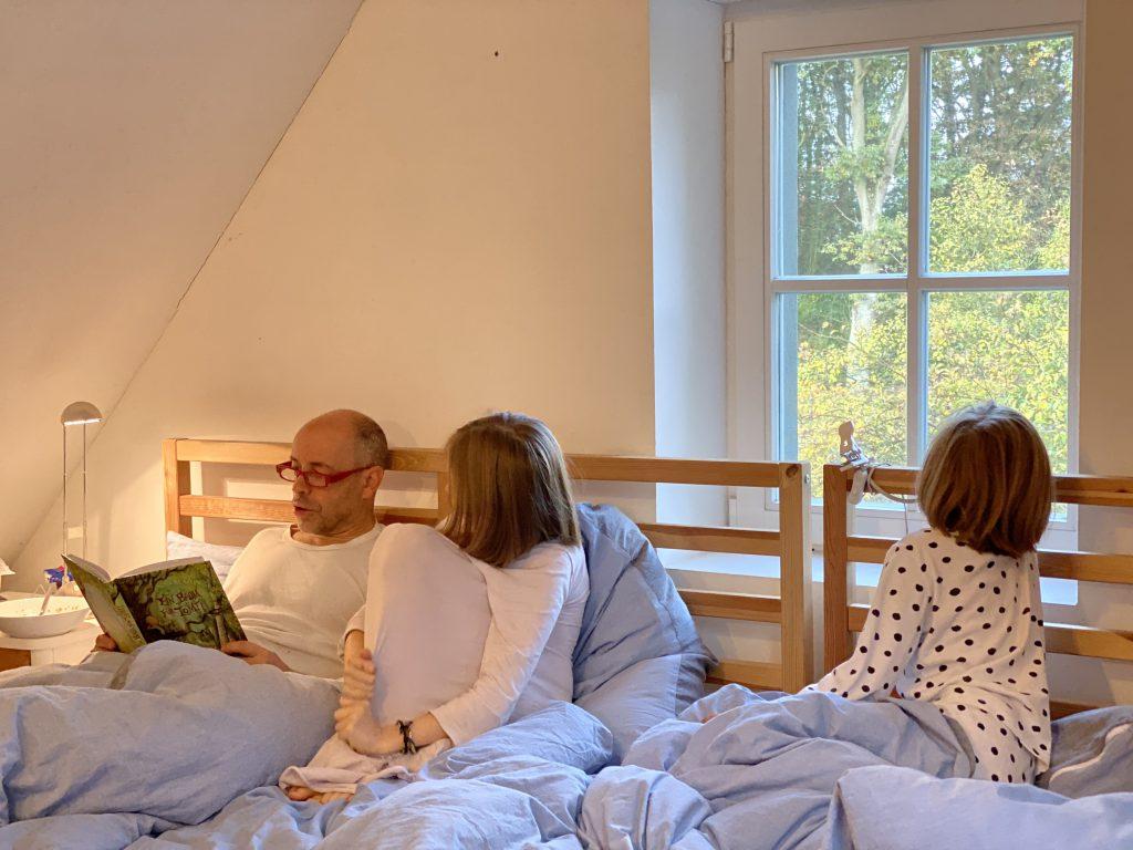 Papa liest zwei Mädchen im Bett vor