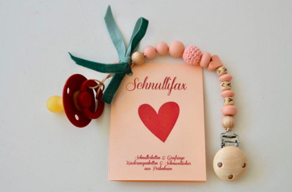 """Warnhinweise Schnullerketten: Vorderseite eines aufklappbaren Beipackzettels mit Ausdruck """"Schnullifax - Schnullerketten & Greifringe - Kinderwagenketten udn Schmusetücher aus Perlenheim"""". Die Schnullerkette ist daran befestigt."""