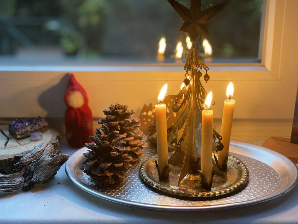 Kerzen-Weihnachtspyramide aus zartem Metall auf Fensterbank