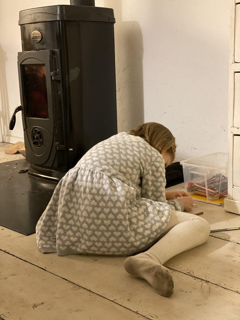 Kind malt auf dem Boden neben Schwedenofen