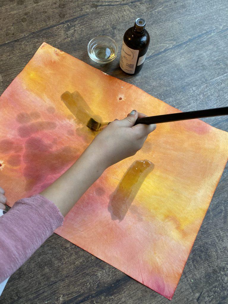 Kind ölt Papier ein zum Falten von Waldorf-Sternenlicht / Knicklicht. Papier ist rot und gelb mit Aquarellfarben bemalt.