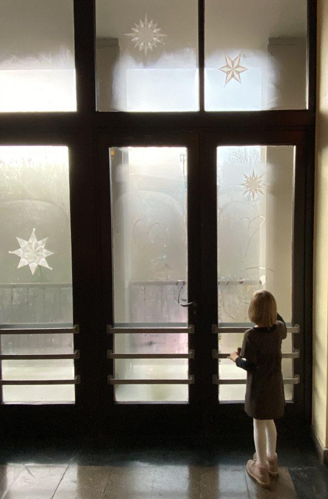Kind (7) vor nebligem Fenster mit weißen Weihnachtssternen