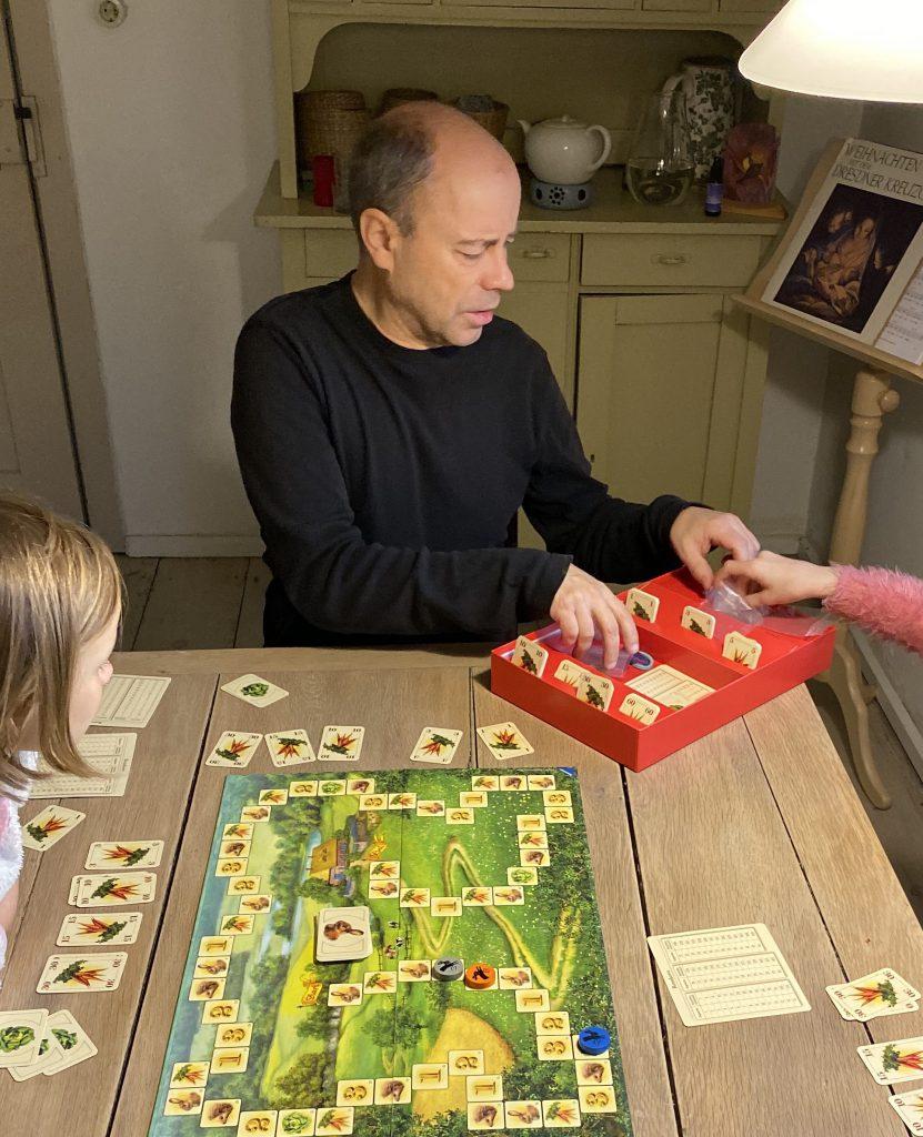"""Mann ordnet Karten in Spielschachtel von """"Hase und Igel"""""""