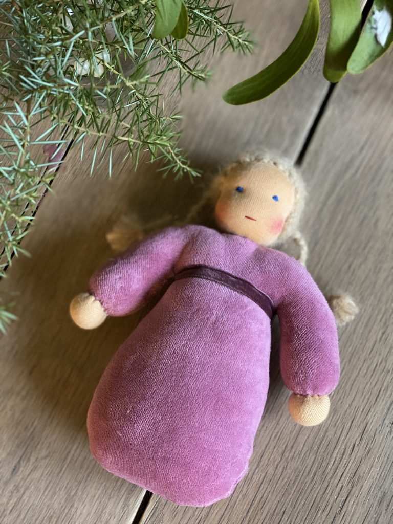 kleine Waldorfpuppe mit blondem Haar auf Holztisch