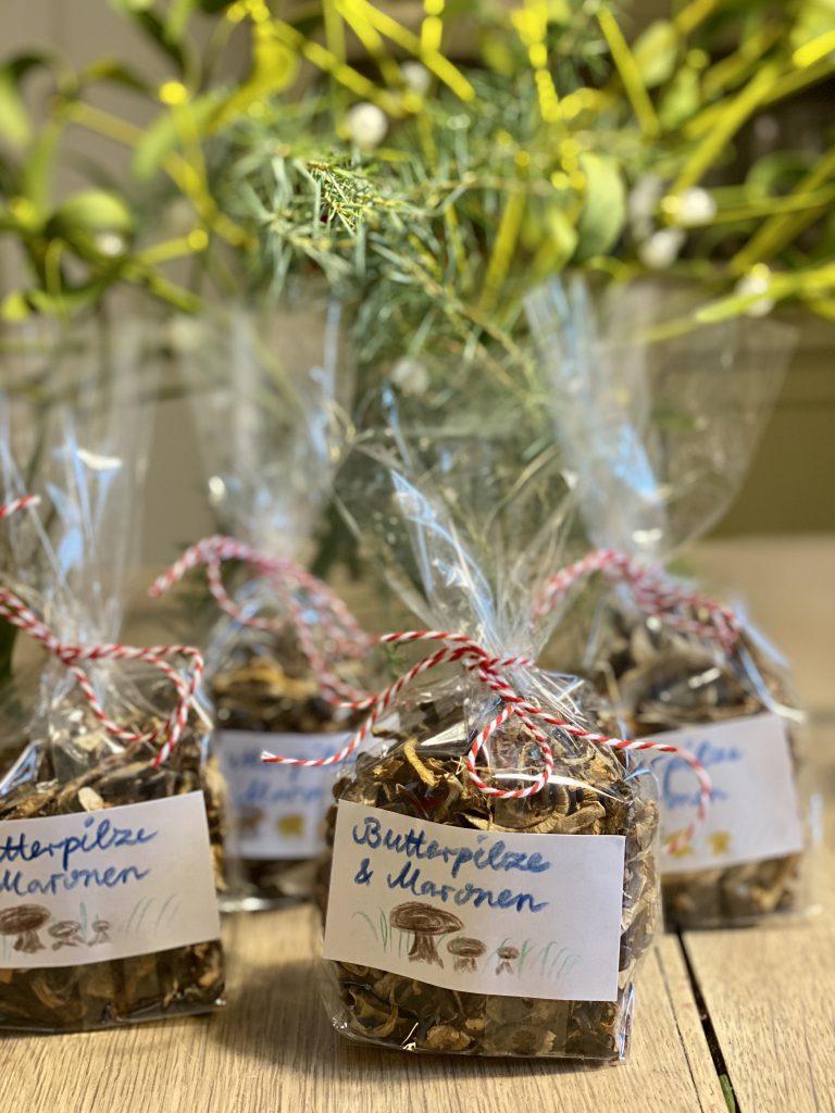 "Zellophan-Tüten mit getrockneten Pilzen und Etikett ""Butterpilze und Maronen"""