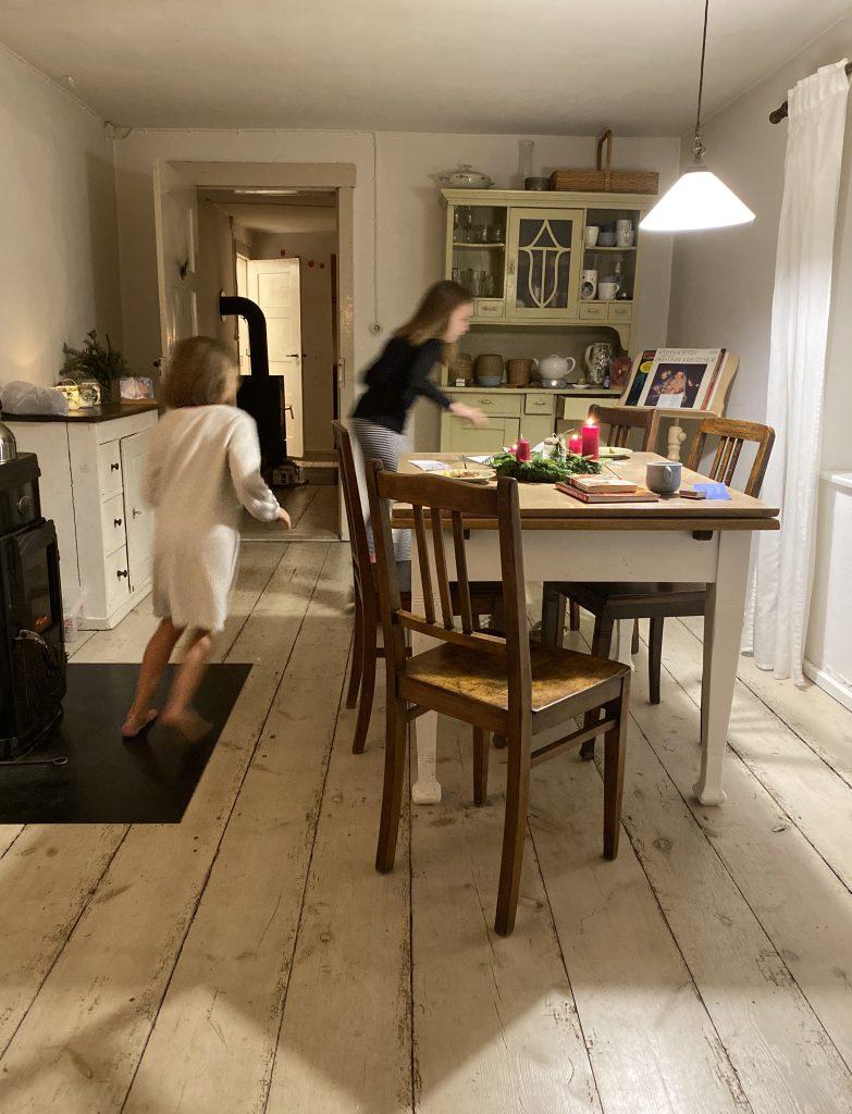 Kinder rennen um Tisch in Bauernstube
