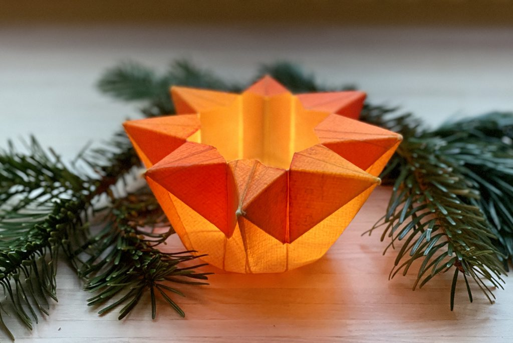 Origami- bzw. Waldorf-Sternenlicht aus orangenem Aquarellpapier, gefaltet, mit brennendem Teelicht darin