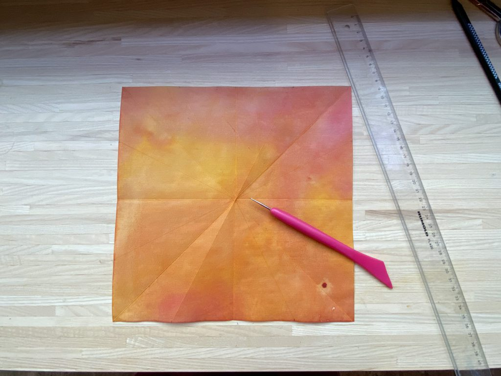 Waldorf Sternenlicht Anleitung: quadratisches Papier liegt auf Tisch, mit Lineal und Falzhilfe