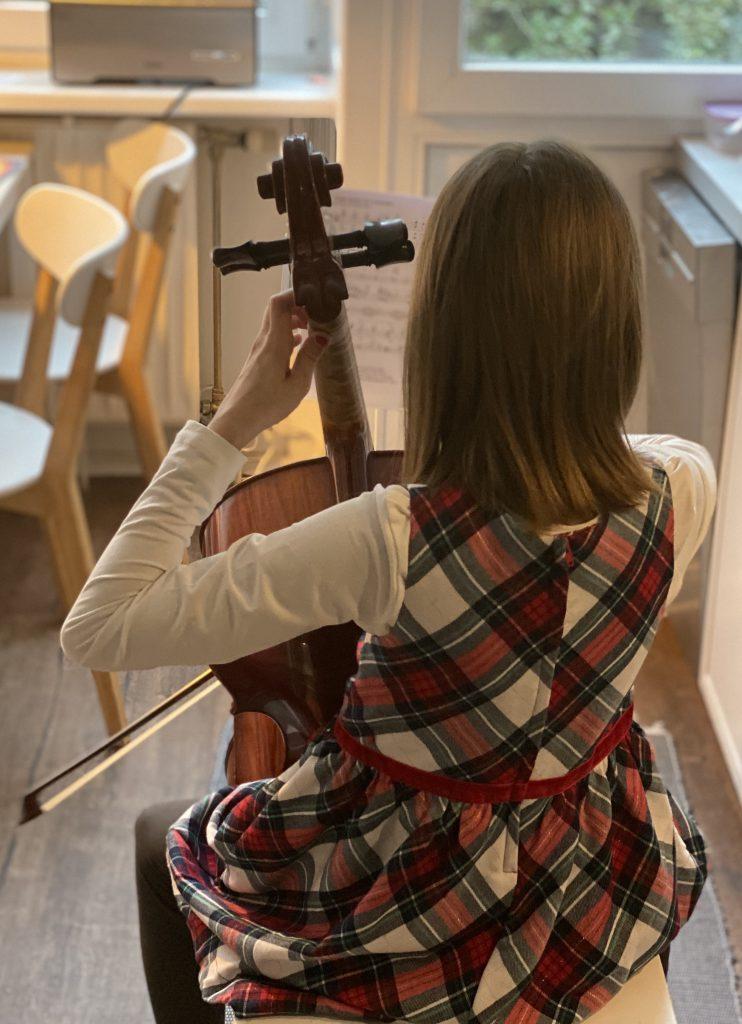 Mädchen 810) spielt Cello (von hinten zu sehen)