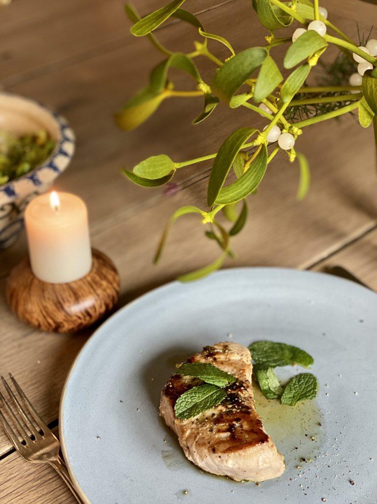 Thunfischsteak auf hellbaumend Teller vor Mistelzweig