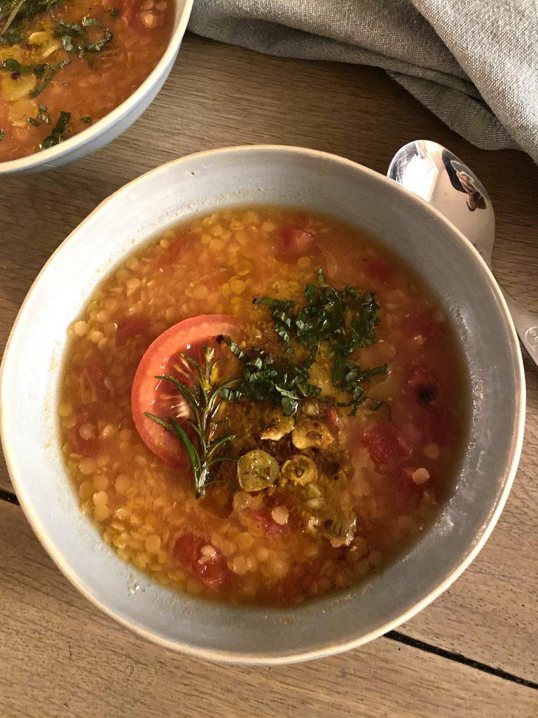 Orangen-Linsen-Suppe in einem Teller, Löffel daneben