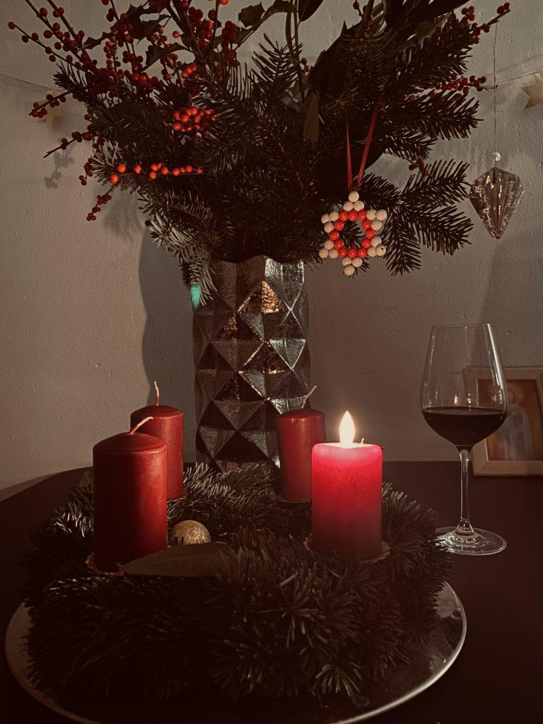 Adventskranz mit 1 brennender Kerze und Weinglas