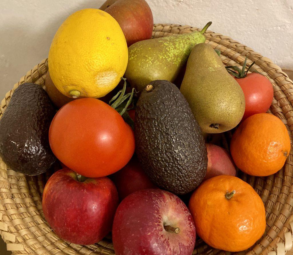 Obstkorb mit Zitrone, Birnen, Tomaten, Äpfeln, Mandarinen, Avocado