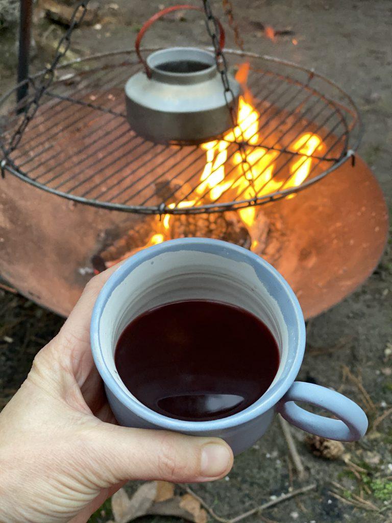 Tasse mit Glühwein vor Feuer mit Kessel