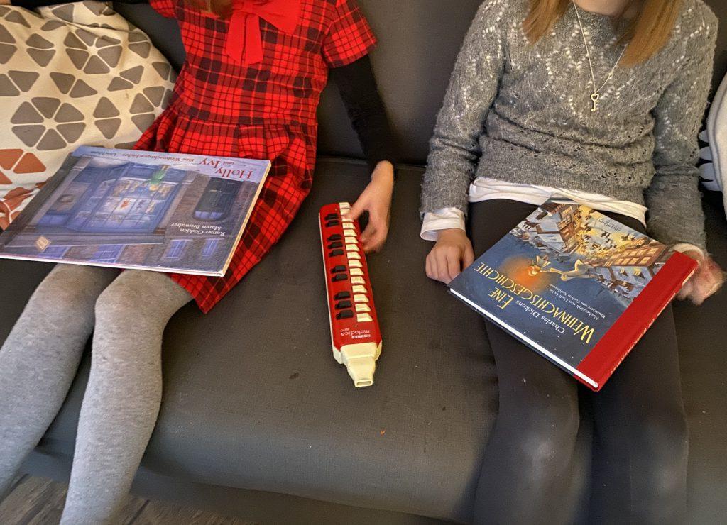 2 Weihnachtsbücher auf dem Schoß von 2 Mädchen, die auf dem Sofa sitzen (ohne Gesichter im Bild)
