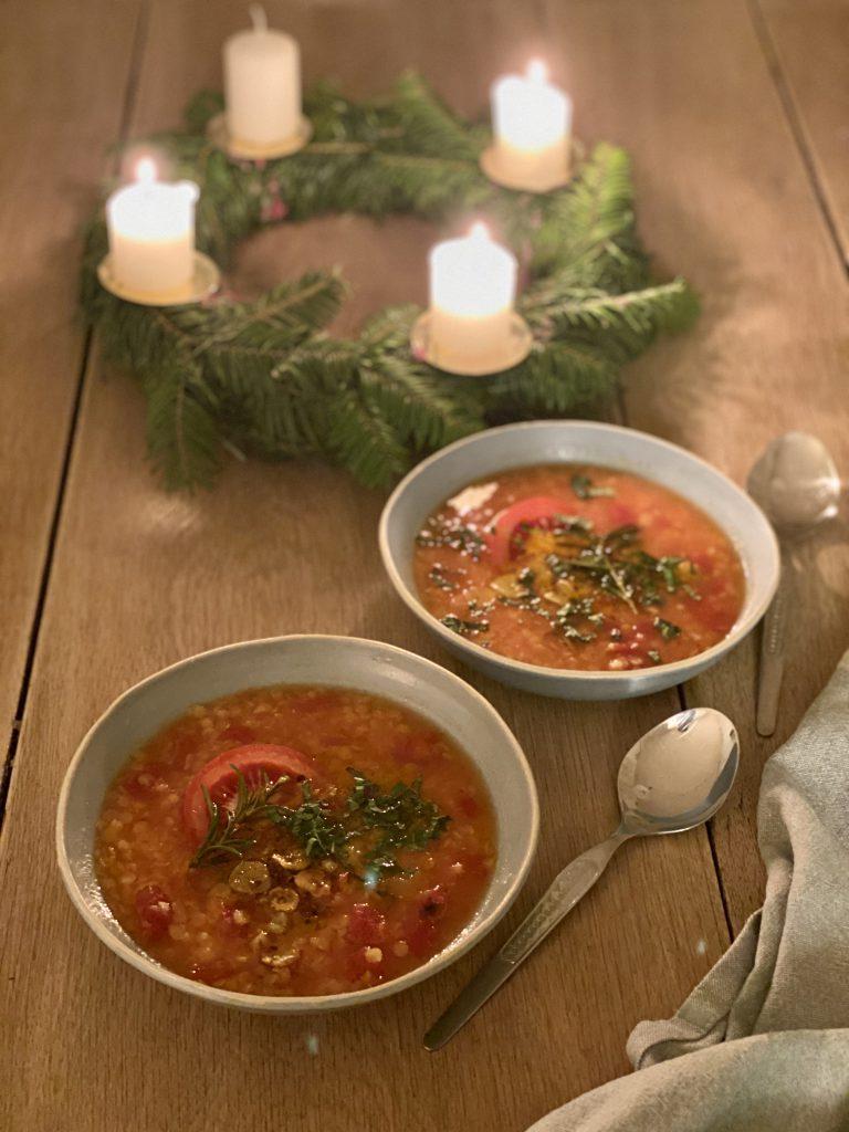 Winterliche Linsensuppe mit Orangen, Tomaten und mediterranen Gewürzen und Kräutern, zwei Teller vor Adventskranz mit drei brennenden Kerzen