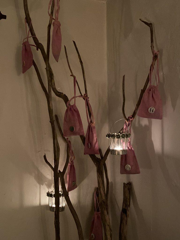 rosa Adventskalender-Beutel an Holzstamm