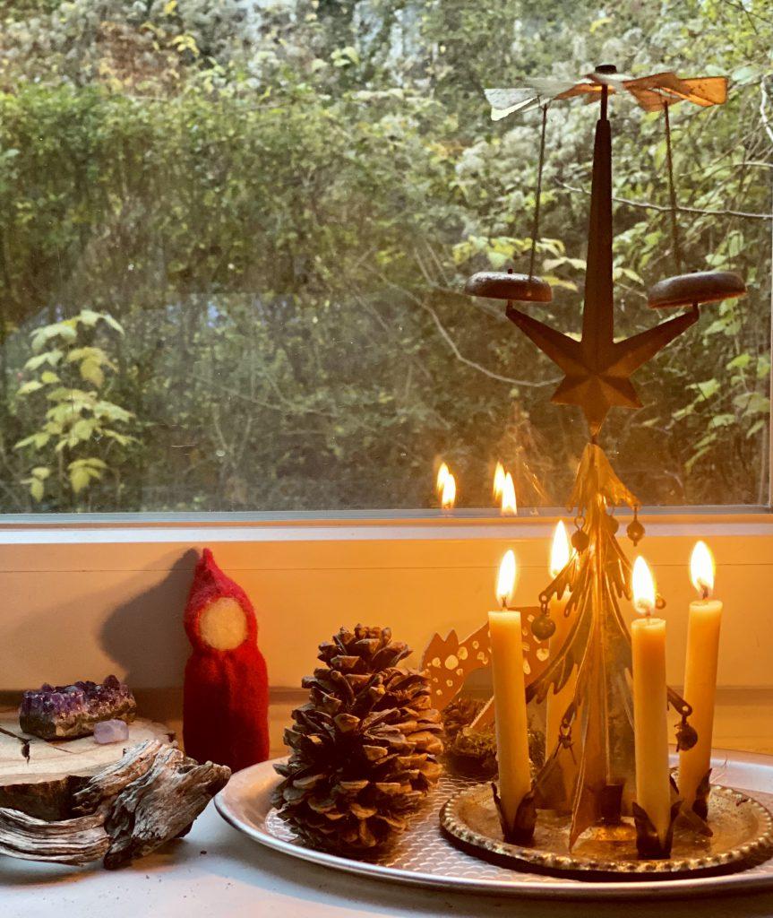 Weihnachtspyramide mit 4 leuchtenden Kerzen auf der Fensterbank