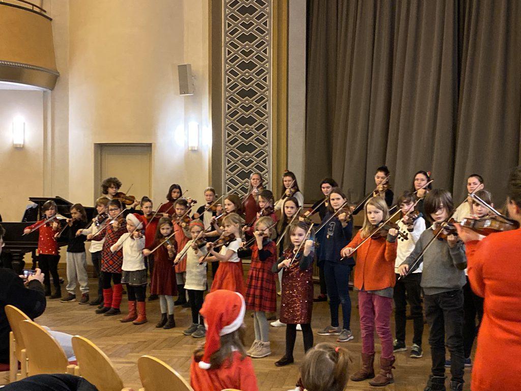 30 Kinder spielen Geige als Chor aufgestellt