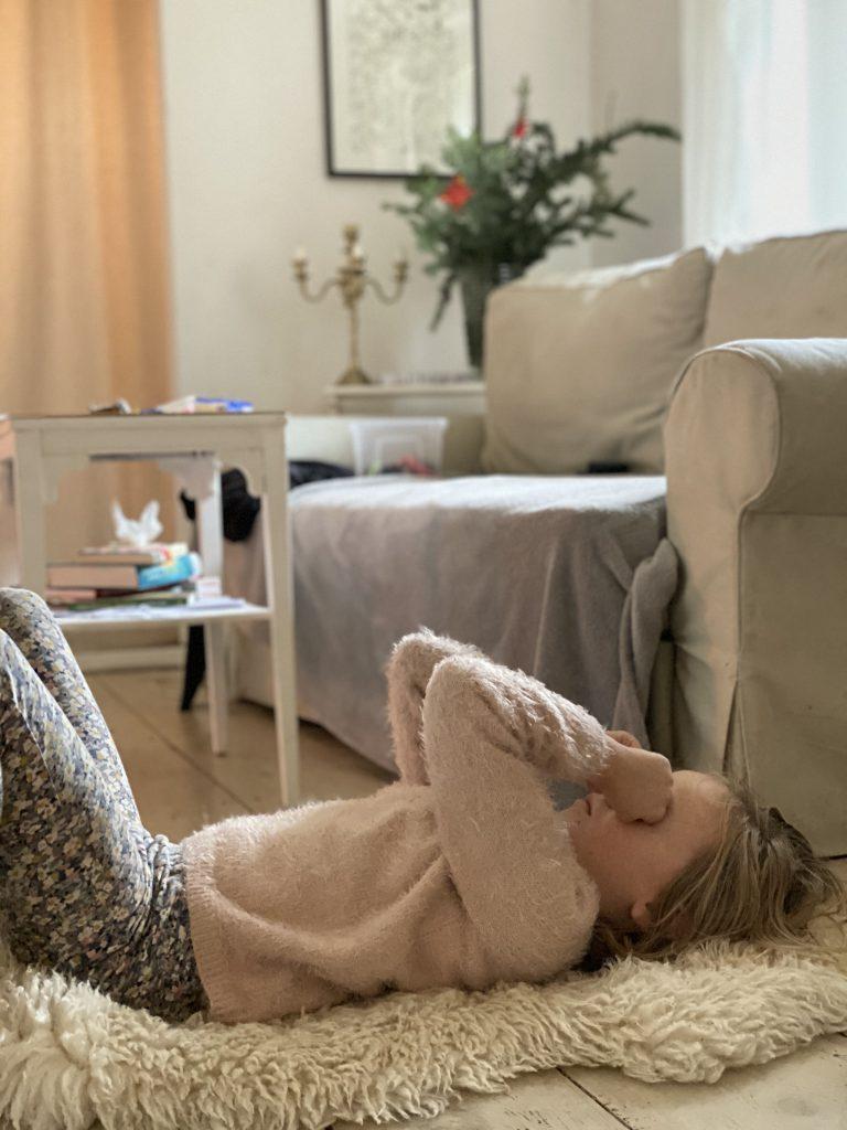 Kind liegt auf Schaffell auf Holzboden und reibt sich die Augen