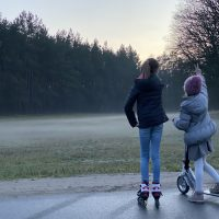2 Kinder mit Roller vor einer Wiese mit Bodennebel