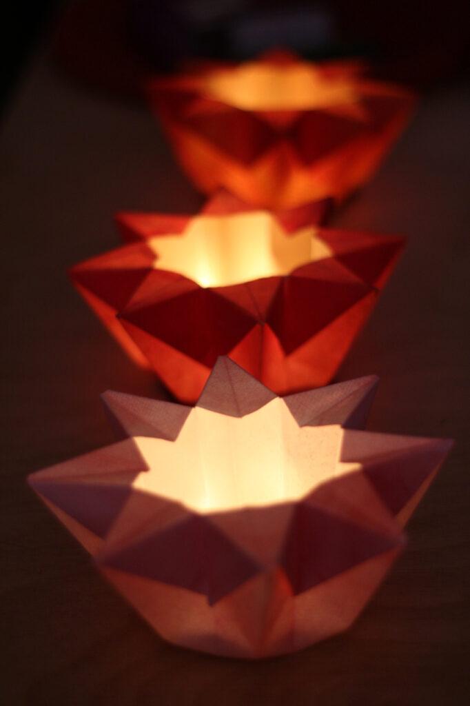 Drei Waldorf-Sternenlichter hintereinander im Dämmerlicht auf Tisch