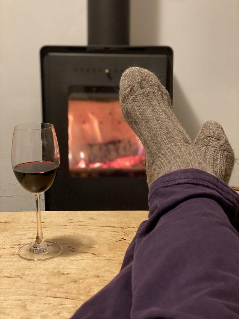 Füße in Strümpfen vor Ofenfeuer, Weinglas auf Tisch