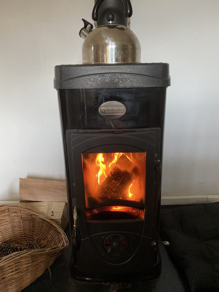 brennender Ofen mit Zapfenkorb daneben