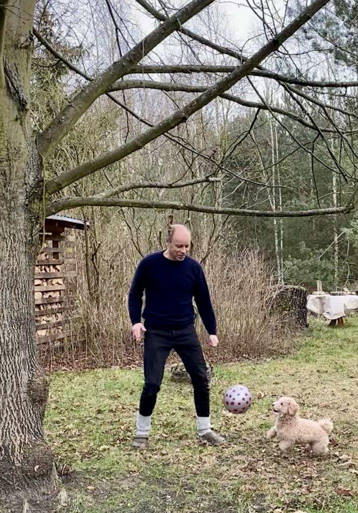 Mann spielt Ball mit Hund vor Schuppen unter Baum (Winter)